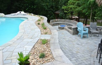 Stone patio with swimming pool and fireplace