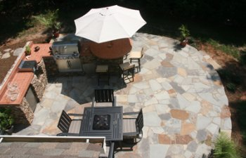 backyard stone patio with an outdoor kitchen