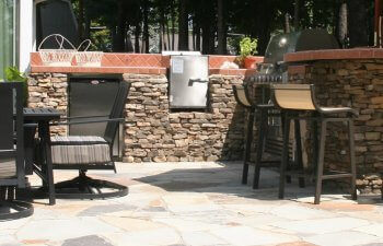 Stone patio with chairs and barbecue